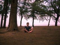 Kleiner Junge, der unter einem alten Baum sitzt und eine Flasche Wasser auf einem Hintergrund von Niederlassungen hält Lizenzfreies Stockbild