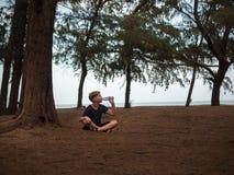 Kleiner Junge, der unter einem alten Baum und einem Trinkwasser von einer Flasche auf einem Hintergrund von Niederlassungen sitzt Lizenzfreie Stockfotografie