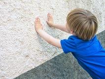 Kleiner Junge, der Verstecken, lehnend an der Wand und am counti spielt Lizenzfreie Stockbilder
