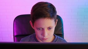 Kleiner Junge, der Videospiele auf seinem Computer, konzentriert auf die Schirmvorratgesamtlänge spielt stock video