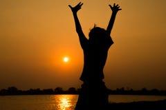 Kleiner Junge, der vor dem Sonnenuntergangschattenbild springt Stockfotos