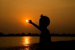 Kleiner Junge, der vor dem Sonnenuntergangschattenbild springt Stockbild