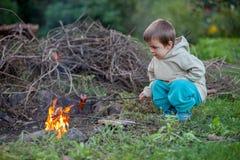 Kleiner Junge, der Würste auf einem Feuer kocht Lizenzfreies Stockfoto