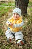 Kleiner Junge in der warmen Kleidung, die auf dem Gras sitzt Lizenzfreies Stockfoto