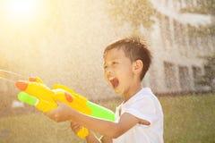 Kleiner Junge, der Wasserwerfer im Park schreit und spielt Stockfoto