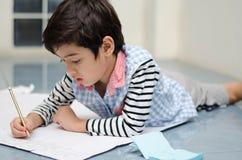 Kleiner Junge, der Weißbuch auf den Boden schreibt stockfoto