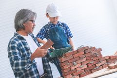 Kleiner Junge, der wie man Backsteinmauer von seinem Baugroßvater lernt, errichtet lizenzfreie stockfotografie