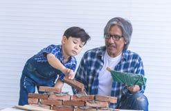 Kleiner Junge, der wie man Backsteinmauer von seinem Baugroßvater lernt, errichtet lizenzfreie stockfotos