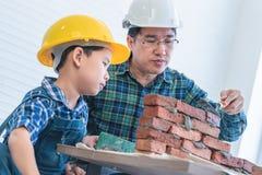 Kleiner Junge, der wie man Backsteinmauer von seinem Bauvater lernt, errichtet lizenzfreie stockfotos