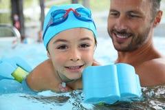 Kleiner Junge, der wie man mit Lehrer lernt, schwimmt Lizenzfreie Stockfotografie