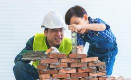 Kleiner Junge, der wie man Ziegelsteinarbeit von seinem Erbauervater lernt, niederlegt stockfotos