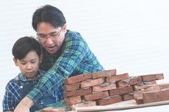 Kleiner Junge, der wie man Ziegelsteinarbeit von seinem Erbauervater lernt, niederlegt stockfotografie