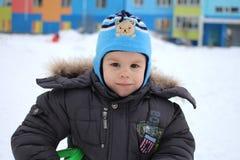 Kleiner Junge, der in Winter im glücklichen Lächeln des Schnees geht lizenzfreie stockbilder