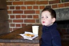 Kleiner Junge, der Wurstrolle und einen Tasse Kaffee isst Stockfotografie