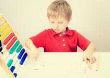 Kleiner Junge, der Zahlspiel mit Abakus lernt Stockfotografie
