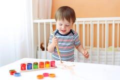 Kleiner Junge, der zu Hause malt Stockbild