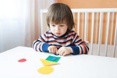 Kleiner Junge, der zu Hause mit geometrischen Zahlen spielt Stockfotografie