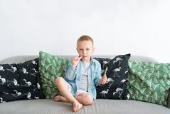 Kleiner Junge, der zu Hause mit Lutscher auf Trainer im Wohnzimmer sitzt Stockbilder