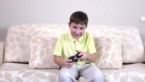 Kleiner Junge, der zu Hause Videospiele, slowmotion spielt stock footage