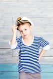 Kleiner Junge, der an zu seiner Kappe hält lizenzfreie stockfotos