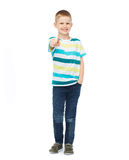 Kleiner Junge in der zufälligen Kleidung seinen Finger zeigend Stockfoto