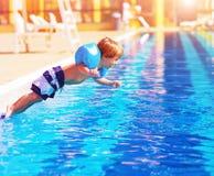 Kleiner Junge, der zum Pool springt Lizenzfreie Stockfotos