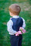 Kleiner Junge, der zurück einen Blumenstrauß von Blumen hinter seinem hält Lizenzfreie Stockfotografie