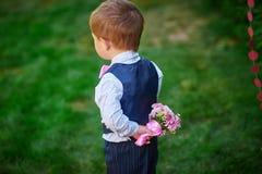 Kleiner Junge, der zurück einen Blumenstrauß von Blumen hinter seinem hält Stockfotografie