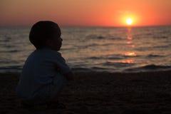 Kleiner Junge, der zurück sitzt und den Sonnenuntergang aufpasst Stockbild