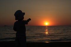 Kleiner Junge, der zurück steht und den Sonnenuntergang aufpasst Stockfotografie