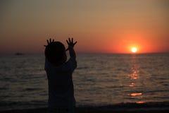 Kleiner Junge, der zurück steht und den Sonnenuntergang aufpasst Lizenzfreie Stockfotos
