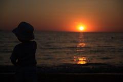 Kleiner Junge, der zurück steht und den Sonnenuntergang aufpasst Stockbilder