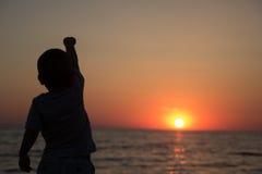 Kleiner Junge, der zurück steht und den Sonnenuntergang aufpasst Stockfoto