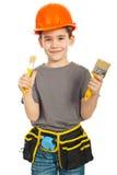 Kleiner Junge, der zwei Lackpinsel zeigt Stockfotografie