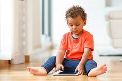 Kleiner Junge des Afroamerikaners, der eine Tasttablette verwendet lizenzfreie stockfotografie