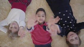 Kleiner Junge des Porträt-schönen Afroamerikaners und zwei kaukasische kleine Mädchen, die an der Kamera beim Lügen auf welle stock video