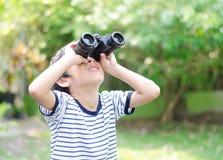 Kleiner Junge, die Abflussrinne schauend Ferngläser Stockfoto