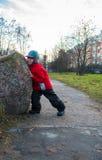 Kleiner Junge drückt einen großen Felsen  Lizenzfreies Stockfoto
