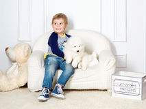 Kleiner Junge drei Jahre alte Spielen mit weißem Welpen Stockfoto