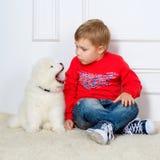 Kleiner Junge drei Jahre alte Spielen mit weißen Welpen Stockfoto