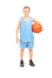 Kleiner Junge in einem blauen Trikot, das einen Basketball hält Lizenzfreie Stockbilder