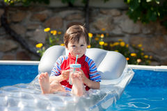 Kleiner Junge in einem großen Swimmingpool, trinkender Saft in einem heißen summe Stockfoto