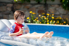 Kleiner Junge in einem großen Swimmingpool, trinkender Saft in einem heißen summe Lizenzfreie Stockfotografie