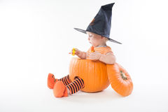 Kleiner Junge in einem Pumpking im Hexenhut, der Süßigkeit hält stockbilder
