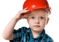 Kleiner Junge in einem roten Aufbausturzhelm Stockbild