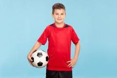 Kleiner Junge in einem roten Trikot, das einen Fußball hält Stockfotos