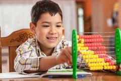 Kleiner Junge erklärt durch Abakus. Selektiver Fokus auf kleinem BO Lizenzfreie Stockfotografie
