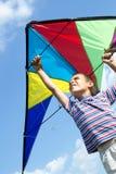 Kleiner Junge fliegt einen Drachen in den blauen Himmel Stockbilder