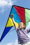 Kleiner Junge fliegt einen Drachen in den blauen Himmel Lizenzfreies Stockbild