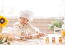 Kleiner Junge in Form eines Kochs stellt den Teig bereit Lizenzfreies Stockfoto